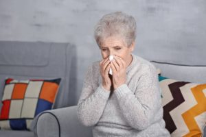 Mature ill woman with tissue at home