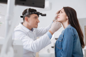 Portrait of otolaryngologist while working with patient