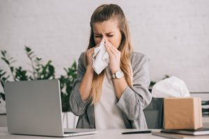 blonde businesswoman sneezing in tissue near laptop in office